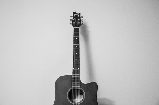 A guitar leaning against a wall